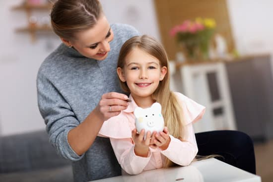 Mother and daughter holding a piggy bank