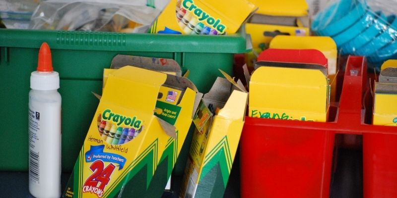 Crayola crayons in red and green totes