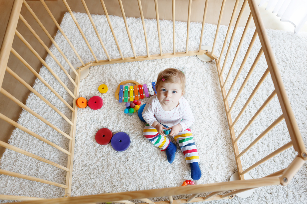 Beautiful little baby girl sitting inside playpen. Cute adorable child playing with colorful toy