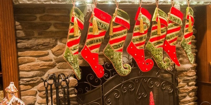 toddler stocking stuffer ideas stockings lined up on stone fireplace